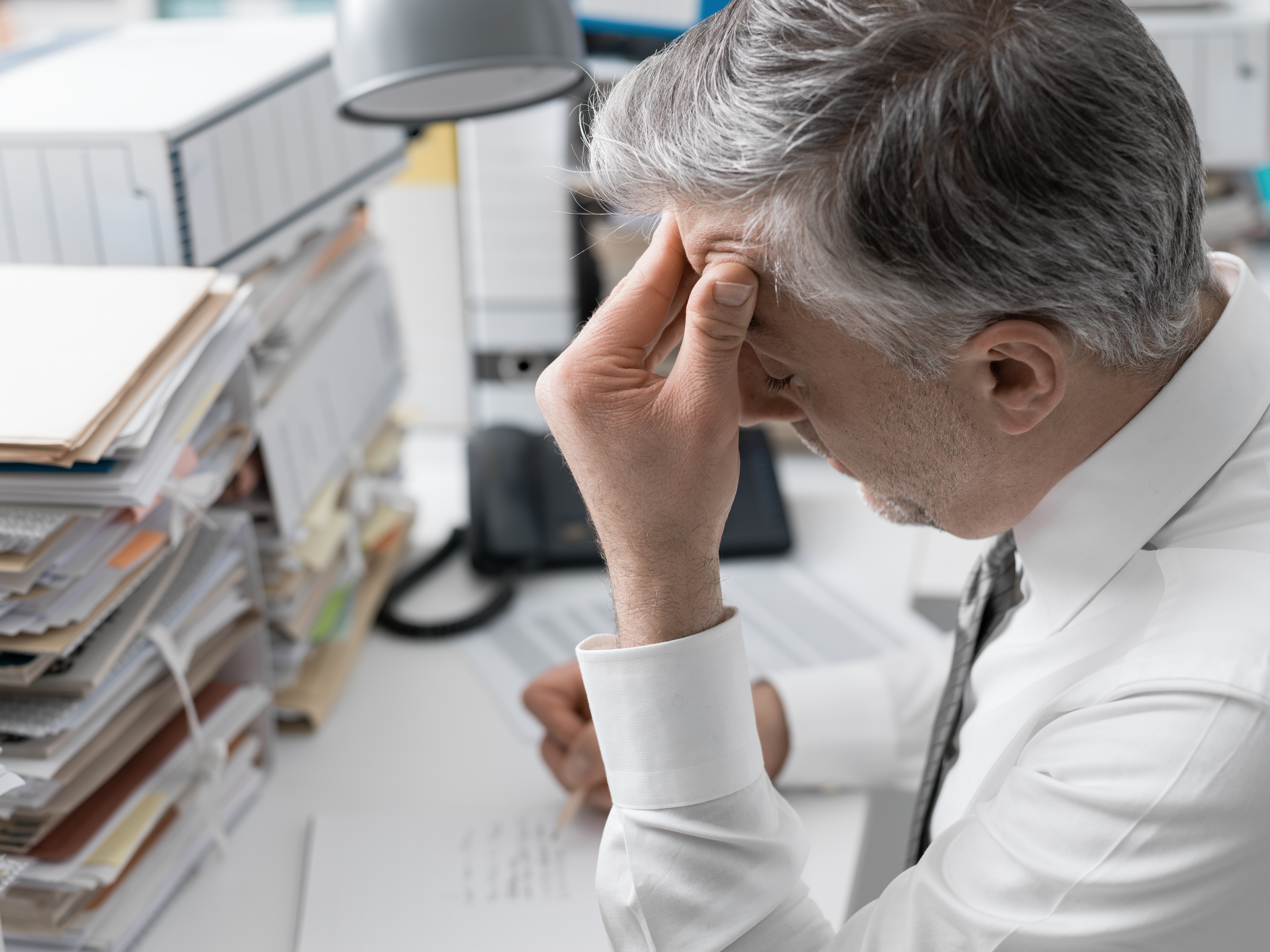 businessman-working-in-the-office-and-piles-of-pap-PN4TDLV